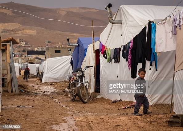 A young Syrian refugee walks past tents at the AlNihaya camp in the eastern Lebanese town of Arsal on October 23 2014 With more than 11 million...