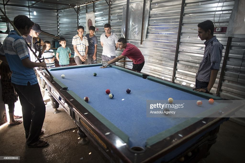 Young Syrian refugees play billiards at a prefabricated billiards saloon at a tent city in the Akcakale District of Sanliurfa, Turkey on September 24, 2015. Turkish Red Crescent provided bank cards for the refugees and gives 85 Turkish Liras every month per person. 260 thousand Syrians who have escaped war and found asylum in Turkey are now living in camps with opportunities that mean they don't miss what they've left behind.