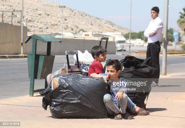 Young Syrian refugees wait for their family to register at the Bab alHawa border crossing after entering Syria from Turkey ahead of the Eid alAdha...