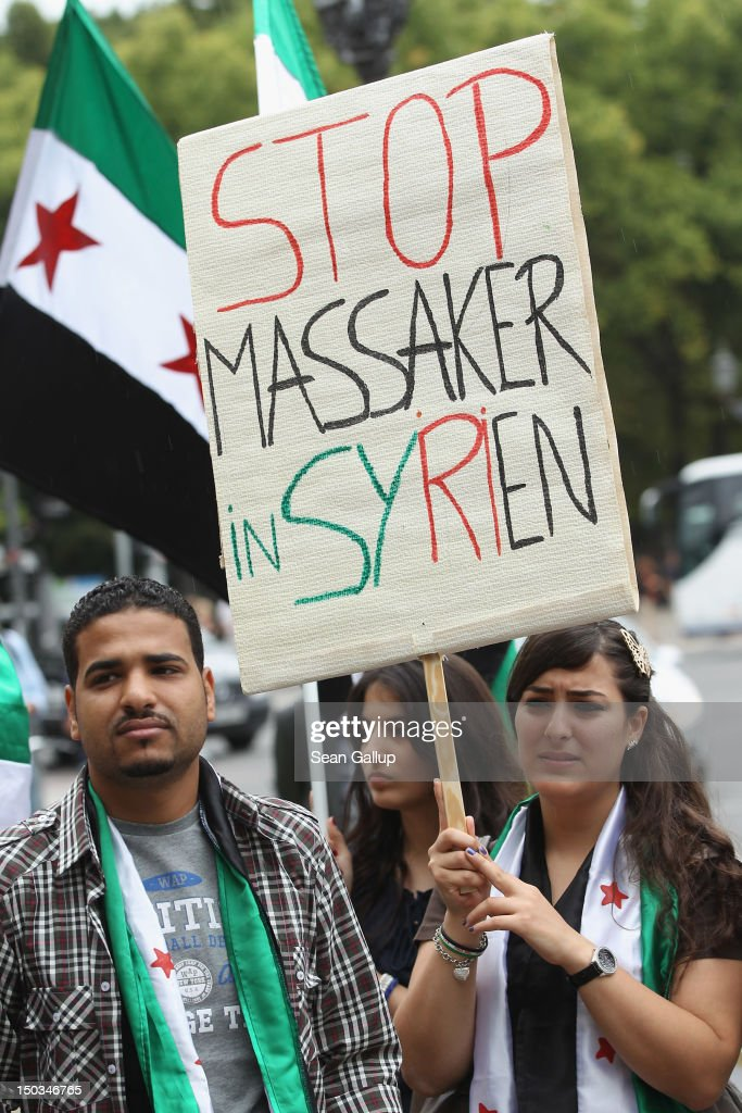 A young Syrian woman holds up a sign that reads: 'Stop [the]Massacre in Syria' at a demonstration of mostly expatriate Iranian opposition activists protesting against Iranian support of the government of Syrian President Bashar Assad on August 16, 2012 in Berlin, Germany. Meanwhile the Organization of Islamic Cooperation suspended Syria's membership during its current summit in Mecca.