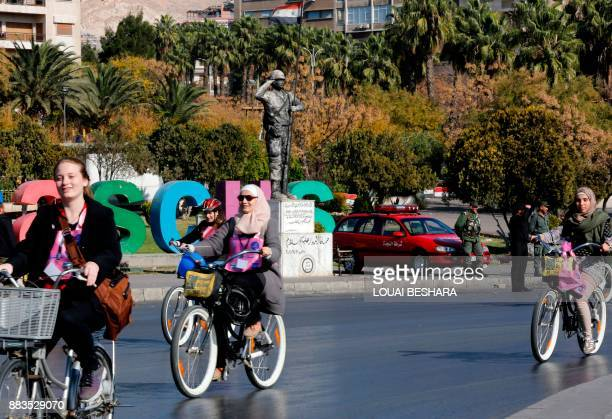 Young Syrian women ride bicycles during a rally in support of the international campaign against violence against women in Damascus on December 1...