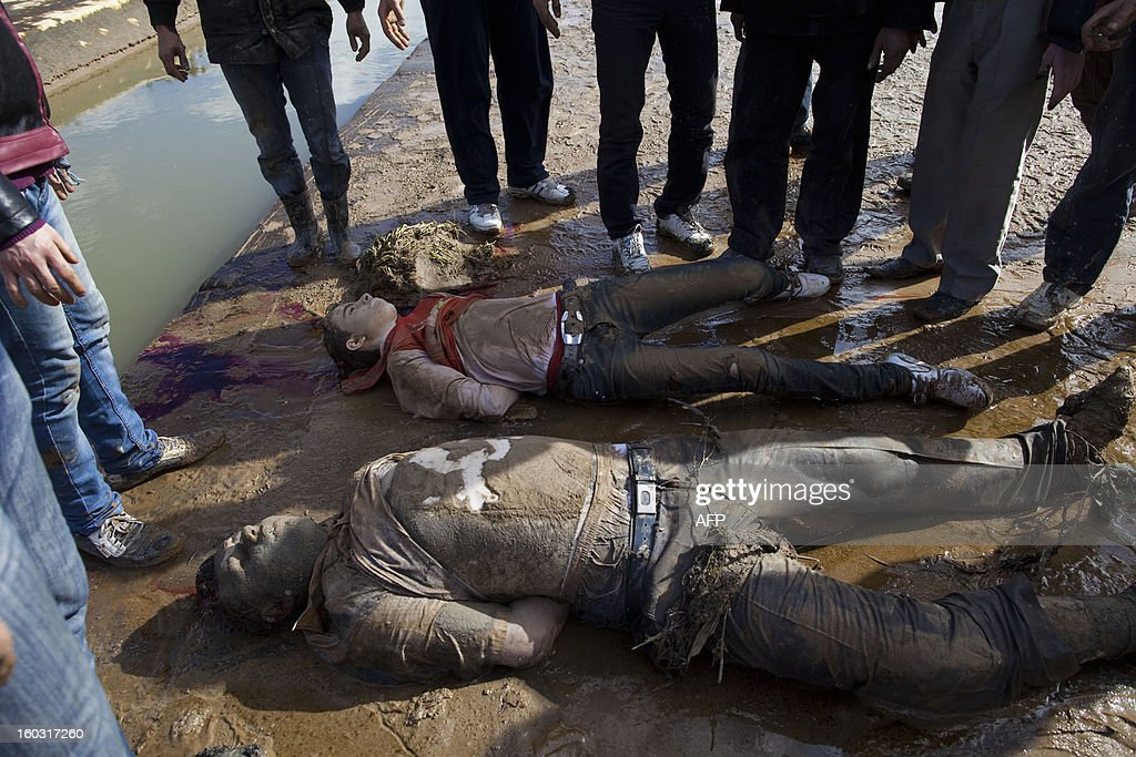 Young Syrians look at the bodies of executed men after being dragged from the water onto the side of a canal in the northern city of Aleppo on January 29, 2013. The bodies of at least 68 unidentified young men and boys, all executed with a single gunshot to the head or neck, were found in the Quweiq River, which separates the Bustan al-Qasr district from Ansari in the southwest of Aleppo, in a rebel-held area where a Free Syrian Army captain said many more were still being dragged from the water.