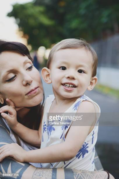 Young tatooed mother holding her son outdoors
