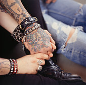 Young Tattooed Couple Holding Hands, Close-up of hands