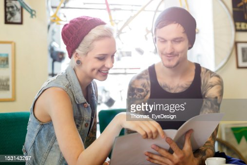 young tattooed man and woman looking at catalogue : Stock Photo