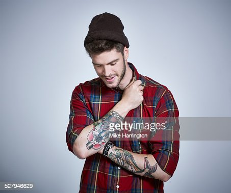 Young tattooed man in check shirt looking to floor