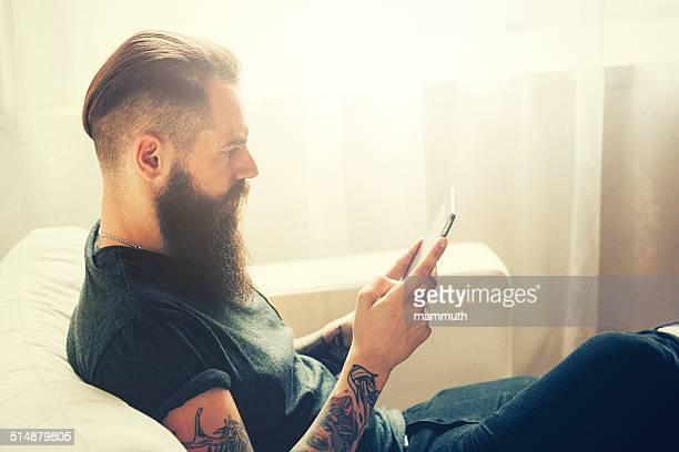 tattooed タブレットを使用して若い男性