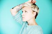 Young tattooed woman on blue