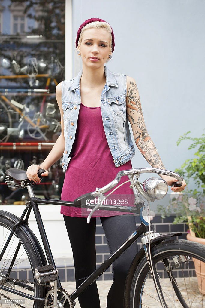Young tattooed woman on her bicycle : Stock Photo