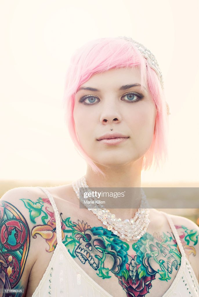 Young tattooed woman with short pink hair : Stock Photo