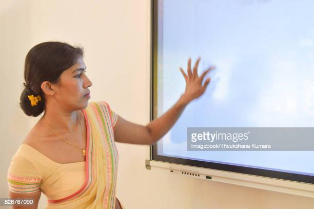 Young teacher touch on Smart board in classroom