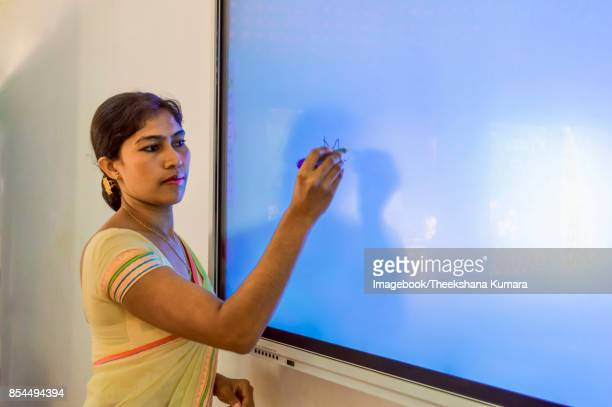 Young teacher write on Smart board in classroom