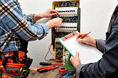 The engineer writes on a notepad the measurement of the voltage of the electrical panel detected by the young electrician