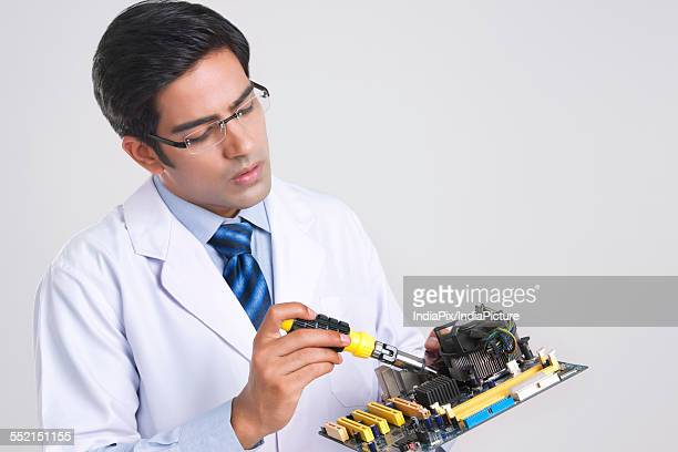 Young technician working on machine part over gray background