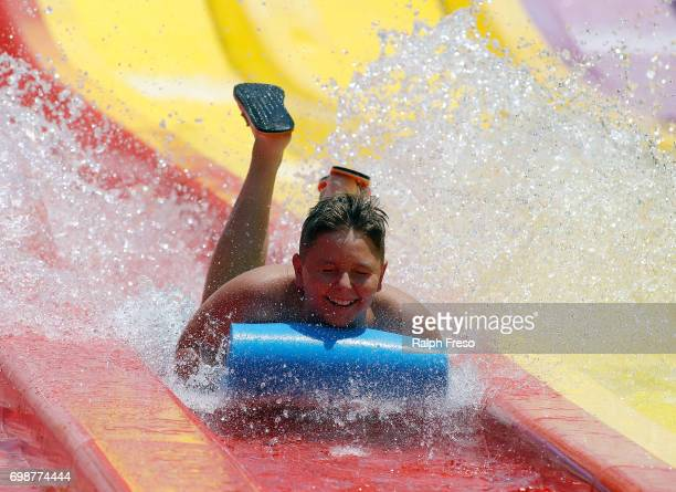 A young teen finds some relief from the heat on a water slide at the WetNWild Water Park on June 20 2017 in Phoenix Arizona Record temperatures of...