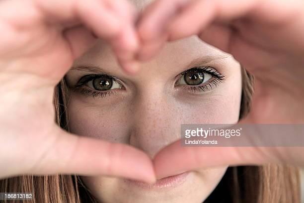 Jeune Teen fille regardant par en forme de cœur