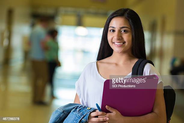 Young teen Indian female student in large high school hallway