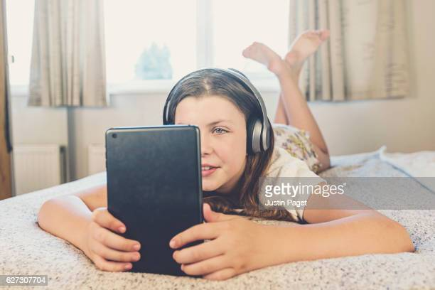 Young Teen listening to music on bed