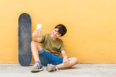 Young teen selfie with skateboard sitting on the floor