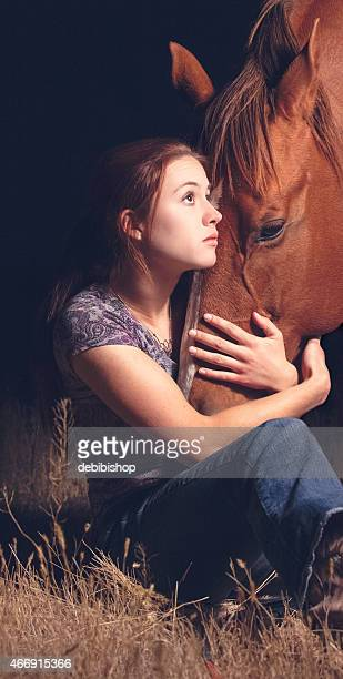 Young teen woman loving her horse with embracing hug