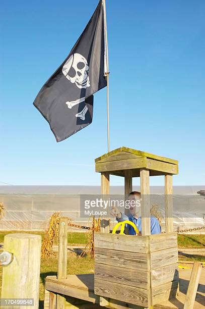 Young Teenage Boy In The Wheelhouse Of A Pretend Pirate Ship In A Playground