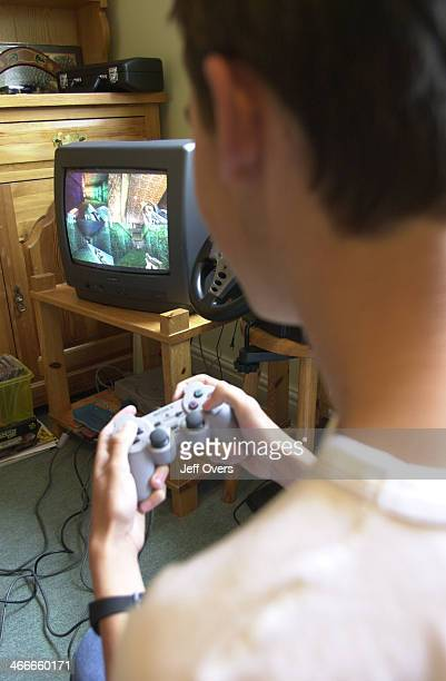 Young teenage boy playing Play Station game at home