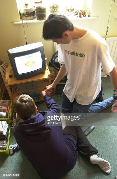 Young teenage boys playing Play Station game at home