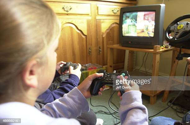 Young teenage girl playing Play Station game at home