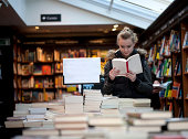 Young teenage girl engrossed in a book in a bookstore