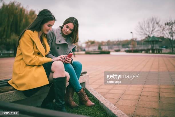 ベンチに座って、携帯電話を使用して 10 代少女