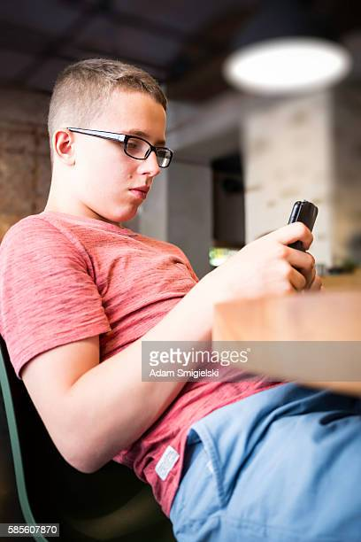 young teenager boy using smartphone in urban setting
