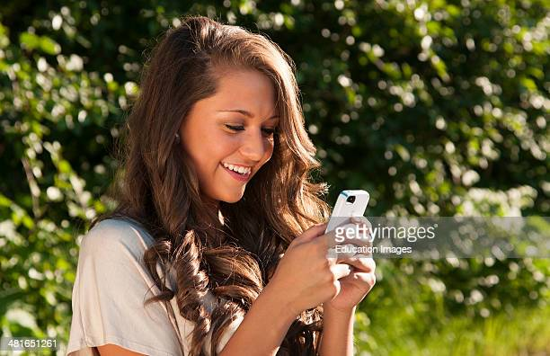 Young teenager girl age 17 texting on IPhone happy home outdoors smiling smile