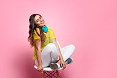 Smiling girl with in casual clothing sitting on chair with big blue headphones.