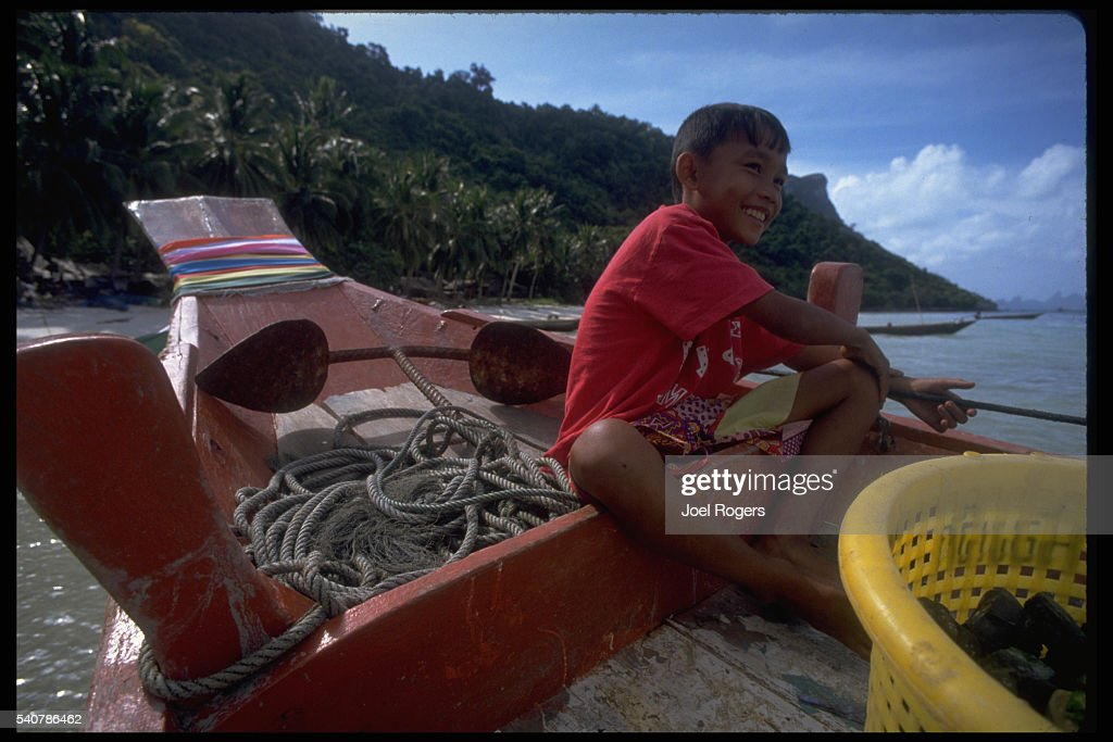 A young Thai boy sits on a boat near the anchor in the Ang Thong National Marine Park in the Gulf of Thailand | Location Ang Thong National Marine...