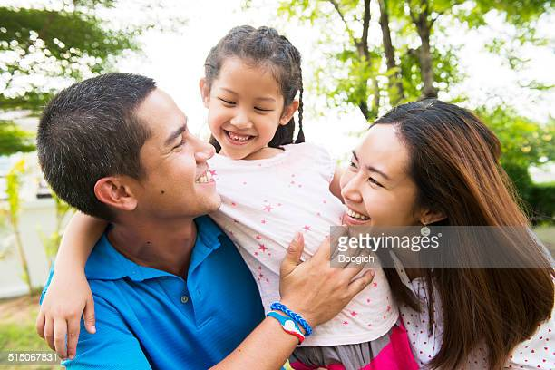 Young Thai Family Spending Time in Front of Home