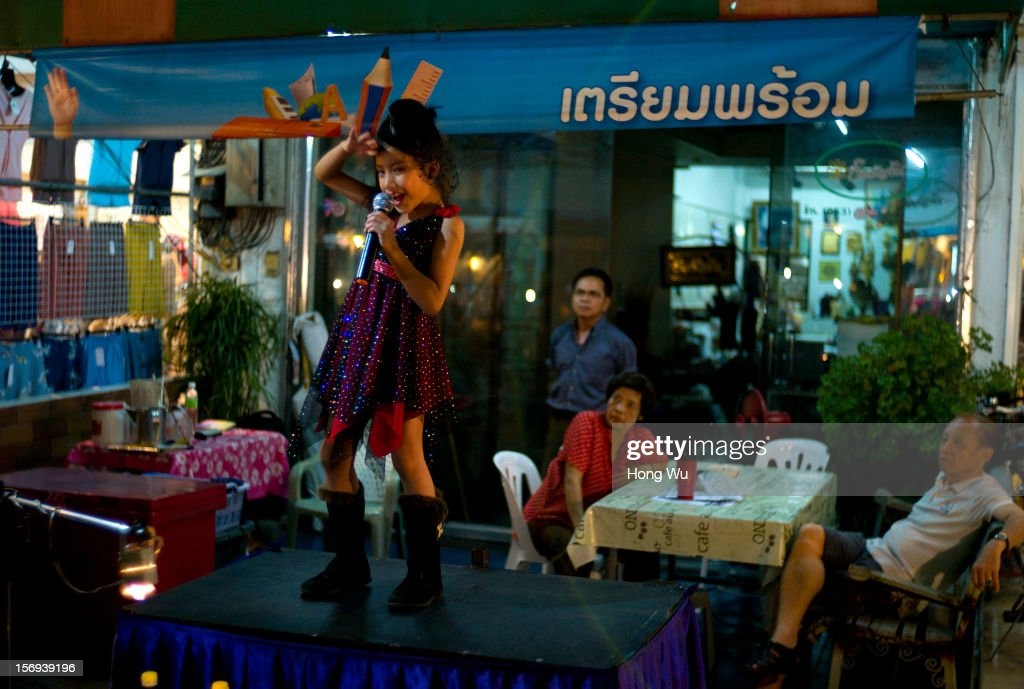 A young Thai girl puts on a singing performance at Chiang Mai Sunday Market on November 25, 2012 in Chiang Mai, Thailand. The Chiang Mai Sunday Market, also called walking Street Market, is held from 4:00 pm until midnight and starts at Thapae Gate, running along the length of Ratchadamnoen Road through the heart of the Old City and is a Chiang Mai institution. Many of the stallholders have personally made the items they sell and the many hand crafted objects are a testimony to the skills and inventiveness of local people, which attracts local citizens and foreign tourists.