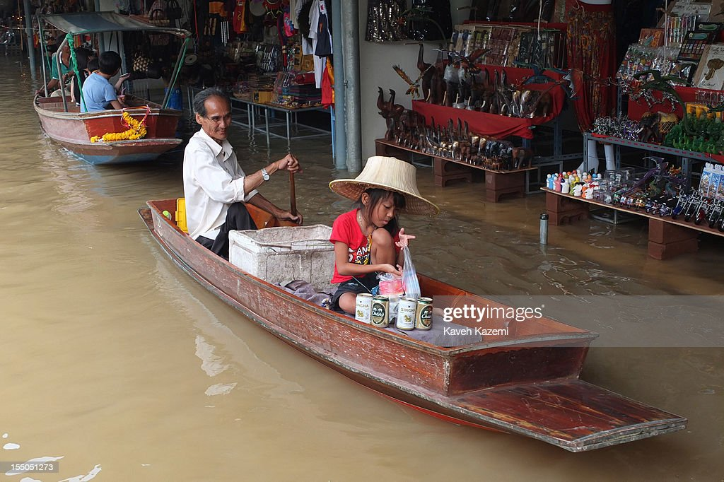 A young Thai girl sat on a canoe with her father sells cold beers in the canal of floating market on October 14 in Damnoen Saduak, Thailand. Damnoen Saduak is a district in the province of Ratchaburi in central Thailand. The central town has become a tourist attraction with its famous floating market.
