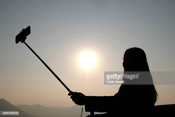 A young Thai woman taking a Selfie at the top of Phu Tok mountain in northern province of Loei in Thailand