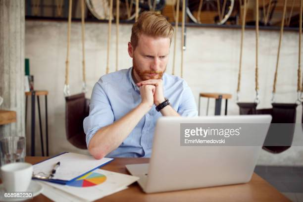 Young thoughtful businessman using laptop during coffee break.