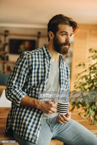 Young thoughtful man with coffee cup relaxing at home.