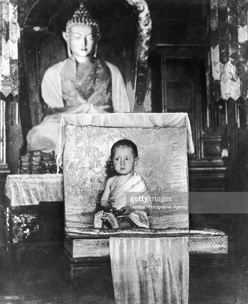 A young Tibetan boy sitting in front of a Buddhist sculpture.