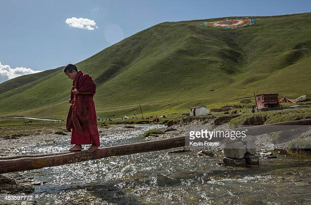 A young Tibetan Buddhist novice monk walks across a beam over a creek at a monastery next to a government resettlement community for former nomads on...