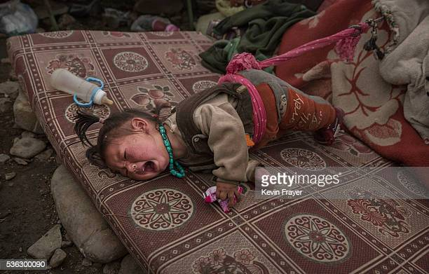 A young Tibetan child from a poor family cries as she sleeps on a mattress at a temporary camp for cordycep pickers on May 23 2016 on the Tibetan...