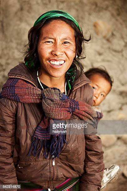 Young Tibetan mother carrying her child