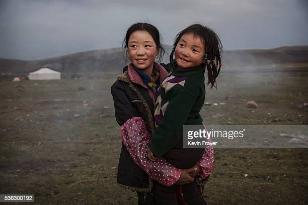 A young Tibetan nomad girl holds her sister at a temporary camp for picking cordycep fungus on May 22 2016 on the Tibetan Plateau near Sershul in the...