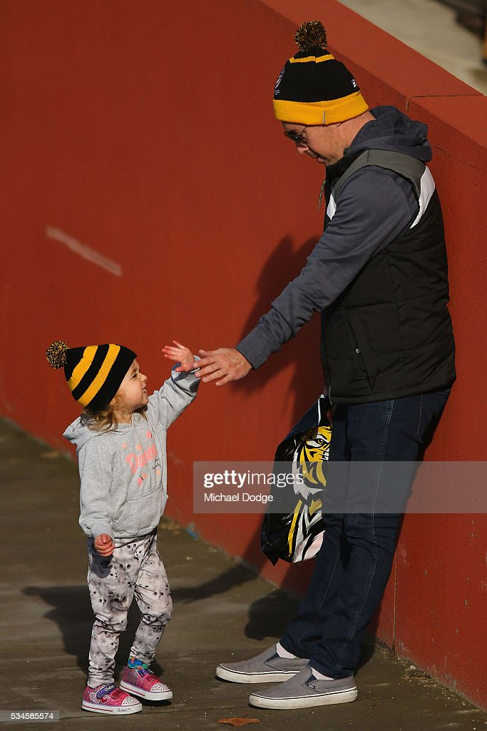 A young Tigers fan arrives with dad during a Richmond Tigers AFL training session at ME Bank Centre on May 27, 2016 in Melbourne, Australia.