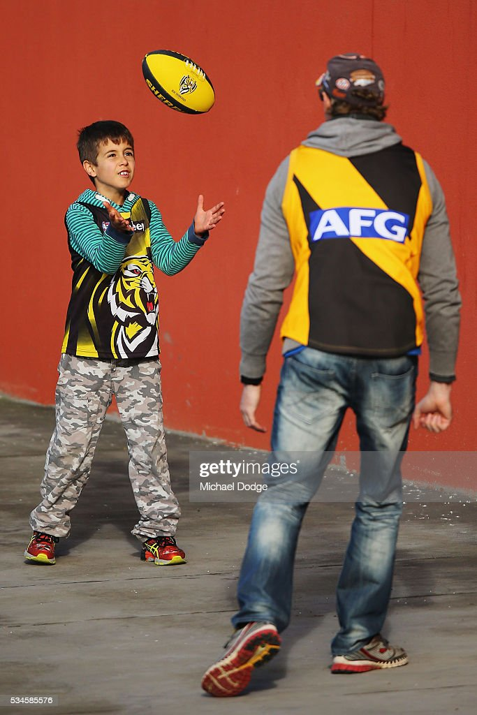 A young Tigers fan plays with dad during a Richmond Tigers AFL training session at ME Bank Centre on May 27, 2016 in Melbourne, Australia.