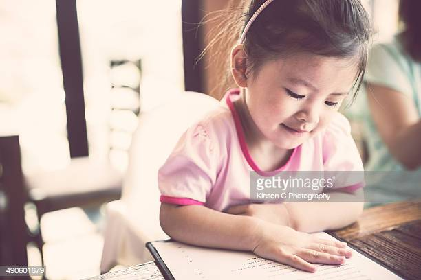 Young toddler at restaurant reading the menu