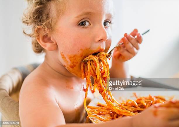 Young toddler boy eating messy pasta