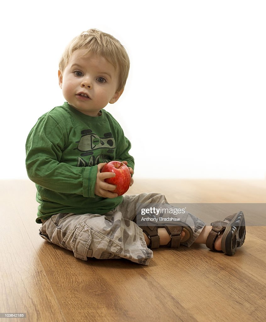 Young toddler holding an apple : Stock Photo